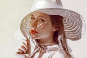 一位漂亮的女人帶這帽子-有陽光在他臉上形成一點一點的光點